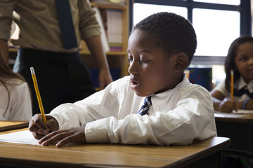 Boy writing on paper while sitting in classroom