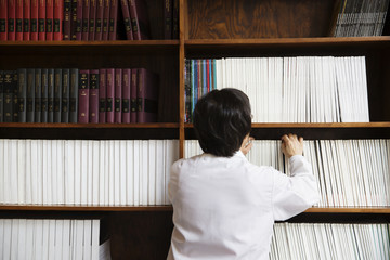 Rear view of female scientist looking for book on shelf