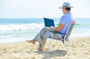 Business man using computer, tropical beach outdoors. Back view