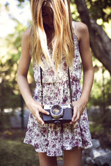 Girl holding camera while standing in yard