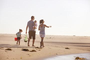 Full length of family walking on beach against clear sky
