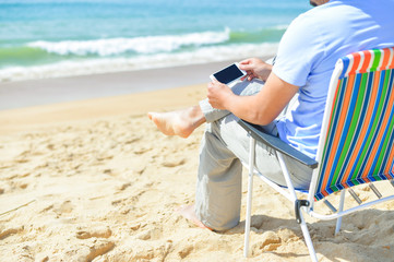 Back side view of young man relaxing on the beach using smartphone