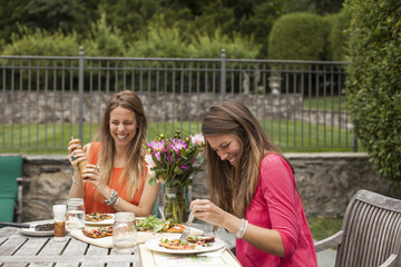 Happy friends having food while sitting at table in lawn