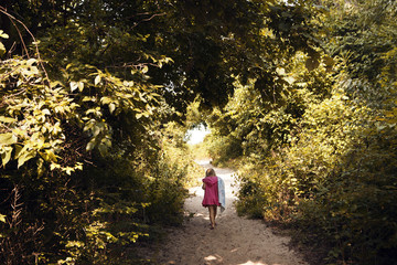 Rear view of girl walking on sand by trees