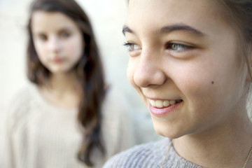 Close-up of happy sisters standing against wall