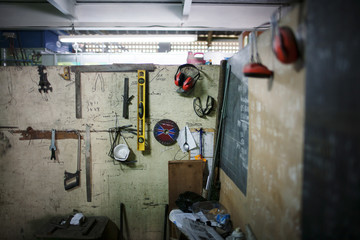Tools and protective workwear hanging on wall