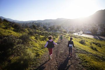 Three children (4-5,  6-7,  8-9) running down footpath,