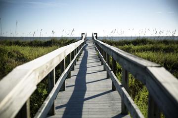 Wooden footbridge leading to sea across swamp