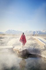 Woman looking at view while standing near hot spring