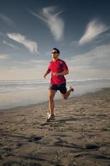 Young man running along beach at sunset