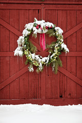 Snow covered wreath on barn during Christmas