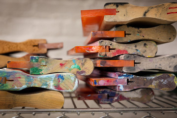 Close-up of squeegees on stand in workshop