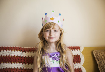 Portrait of girl wearing crown while sitting on bed at home