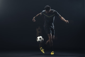 Young athlete playing soccer against black background