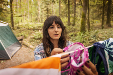 Woman drying bra on clothesline while camping in forest