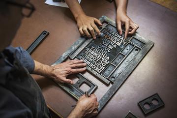 Men assembling text on print at workshop