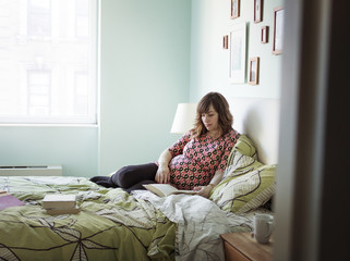 Pregnant woman reading a book while sitting on bed