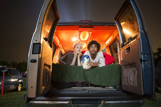Couple watching drive-in movie from the back of van