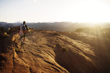 Man hiking on rock formation at sunset