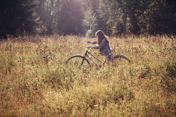 Girl walking with bike in meadow
