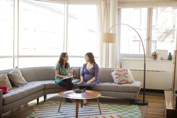 Doctor talking to pregnant woman while sitting on sofa at home