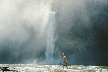 Man with stick walking in river against waterfall