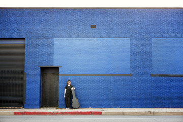 Man with guitar case standing on footpath against blue brick wall