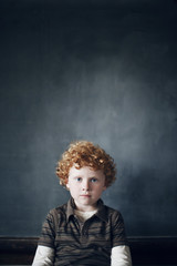 Portrait of schoolboy with red hair in classroom