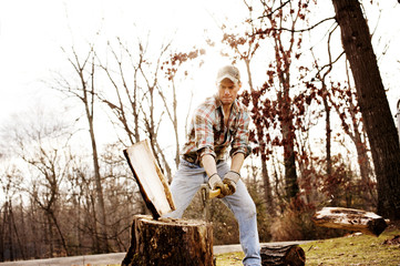 Lumberjack cutting log on tree stump at forest