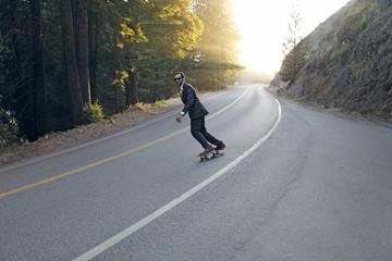 Man in suit skateboarding on empty road
