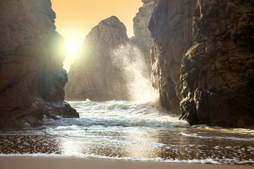 Fantastic big rocks and ocean waves at sundown time