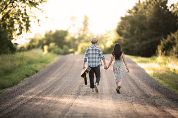 Young couple walking along dirt road and holding hands
