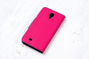 Hot pink colored wallet case cover for mobile phone on vintage wooden background