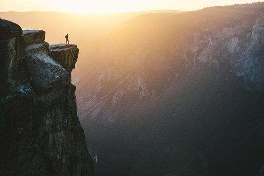 Man standing on mountain peak during sunset
