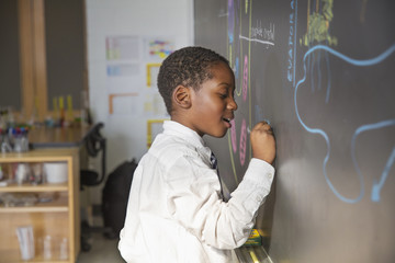 Side view of boy drawing on blackboard during lesson in classroom