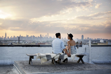 Rear view of couple talking while sitting on bench at building terrace during sunset
