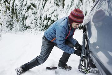 Man repairing his car in snowy landscape