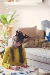 Girl drawing christmas tree on paper