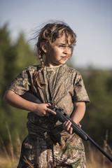 Girl (6-7) holding hunting rifle