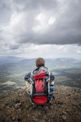 Hiker sitting on top of mountain peak