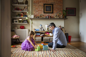 Father looking at girl playing with toys while sitting on floor at home