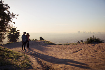 Couple walking on hill at sunset