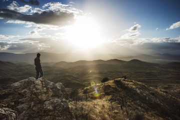 Hiker standing on rock by mountains against sky on sunny day