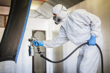 Worker in protective workwear spray painting in hangar