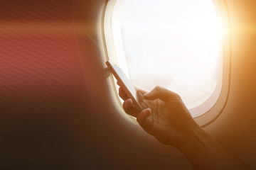 holding mobile phone with flight mode in the airplane