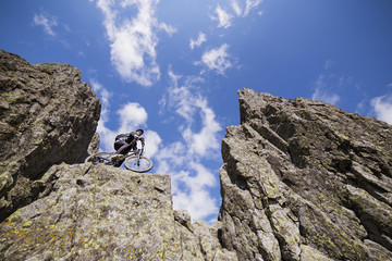 Upward view of biker cycling on rock