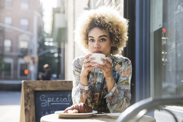 Young woman drinking coffee in sidewalk cafe,