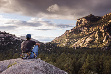 Hiker sitting on rock while watching mountains against cloudy sky