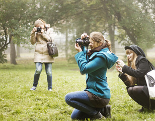 Friends photographing on grassy field at park