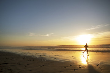 Silhouette of young man running along beach at sunset